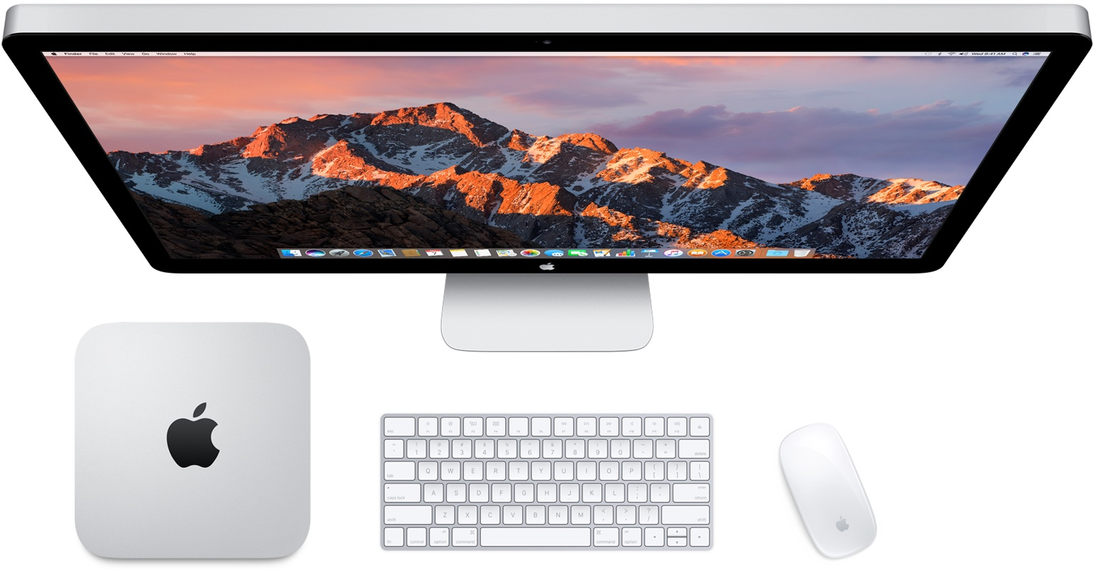 An image depicting an overhead view of an iMac along with a Mac mini, Apple wireless keyboard and mouse