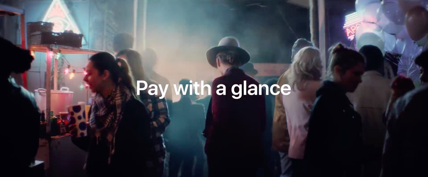 """A still from an Apple Pay ad with the tagline """"Pay with a glance"""" shown centered in the middle of the screen"""