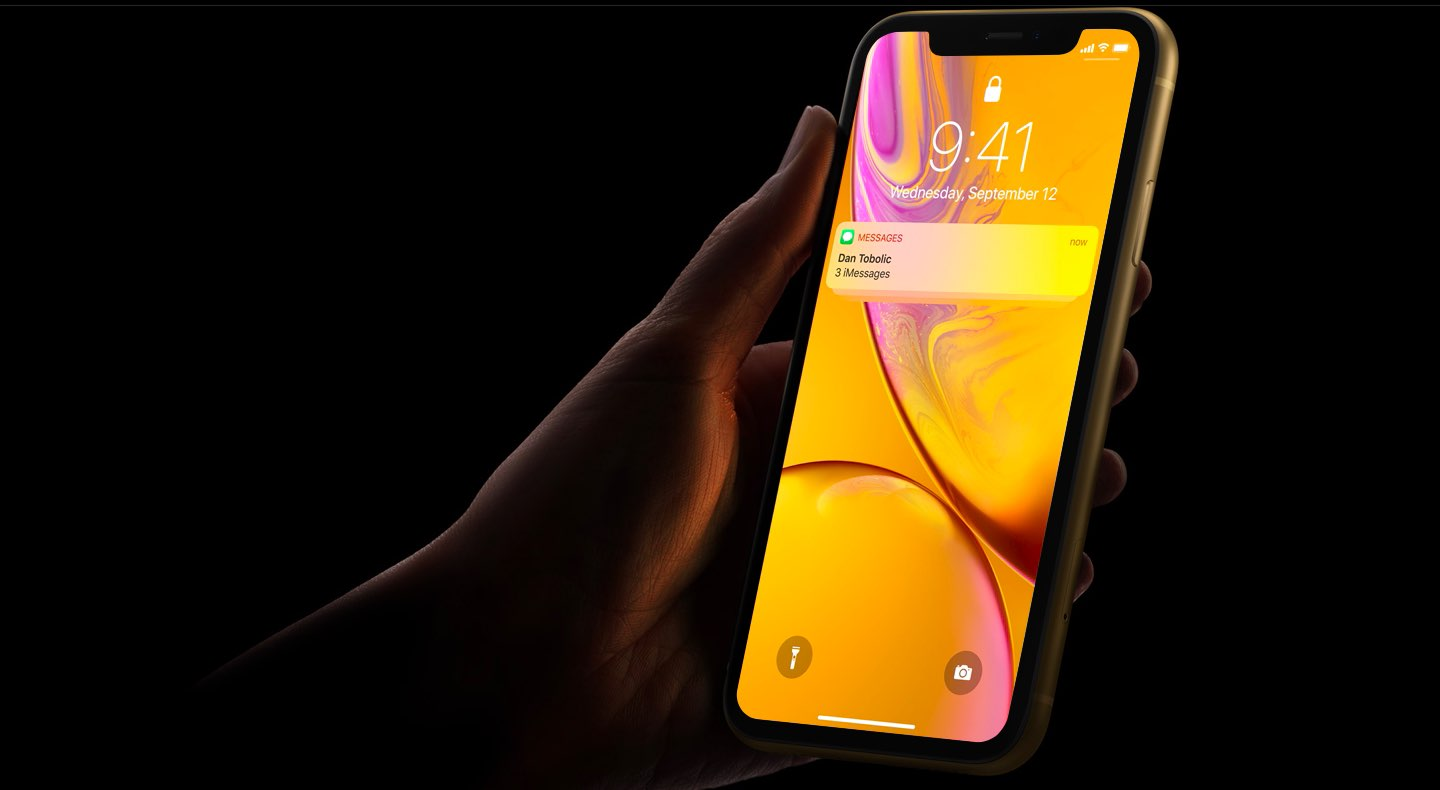 An image showing an iPhone XR held in hand, set against a dark background, with a Messages notification shown on the lock screen