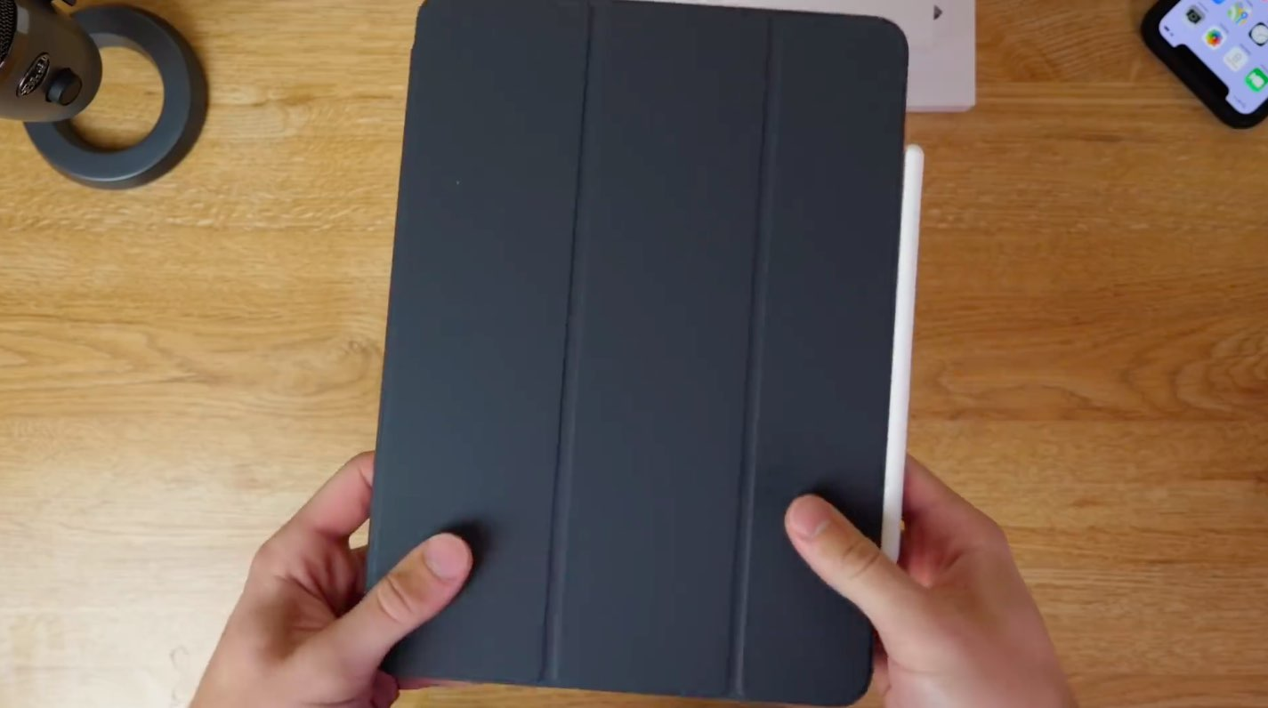 A photo showing an iPad Pro in a Smart Folio case, held in hand