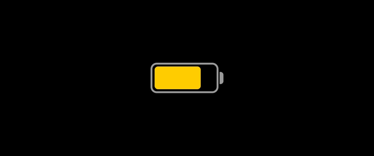 An illustration showing a yellow battery icon indicating Apple's low power mode set against a completely black background