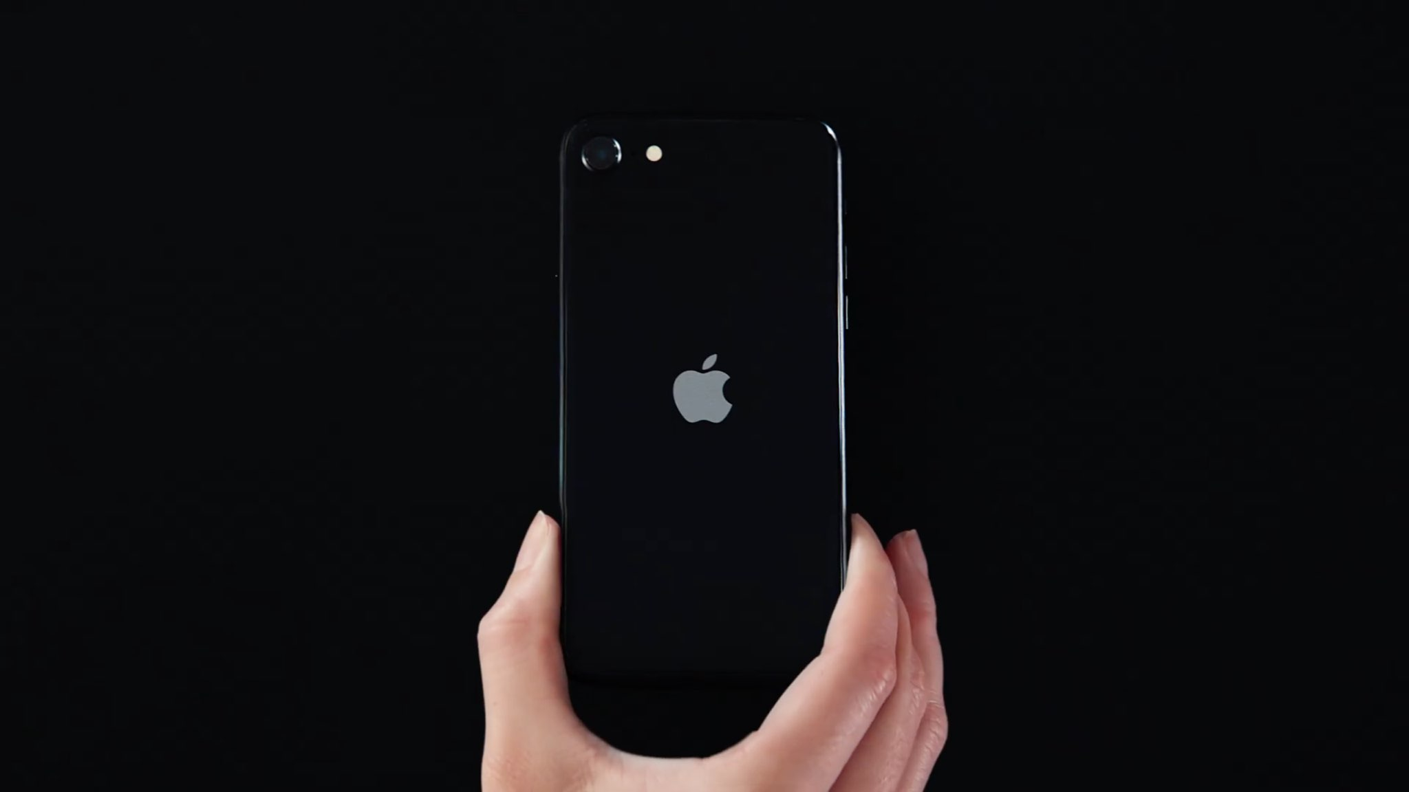 A still from Apple's commercial for the iPhone SE showing a hand laying a matte black iPhone SE on an all-black surface