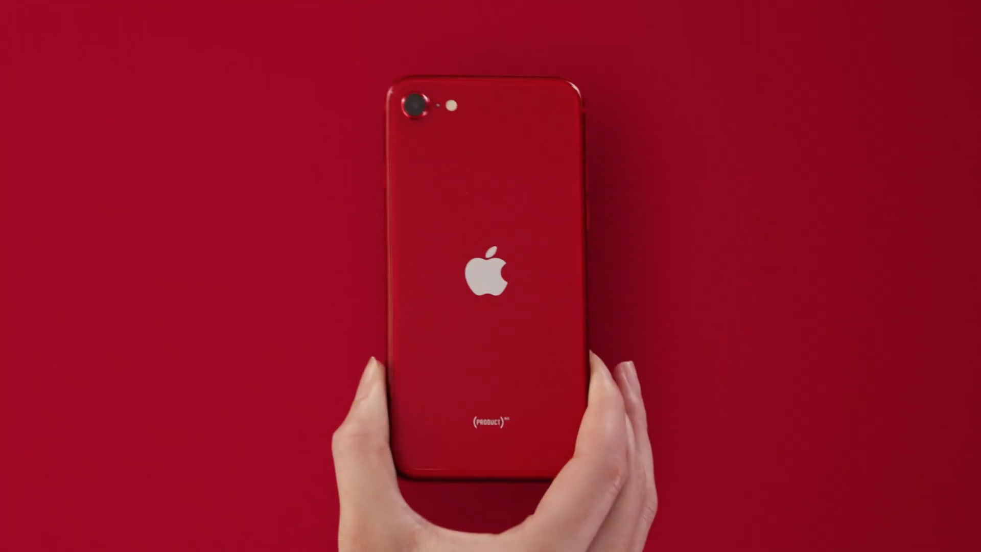 A hand showing holding a red iPhone SE 2, set against an all-red background