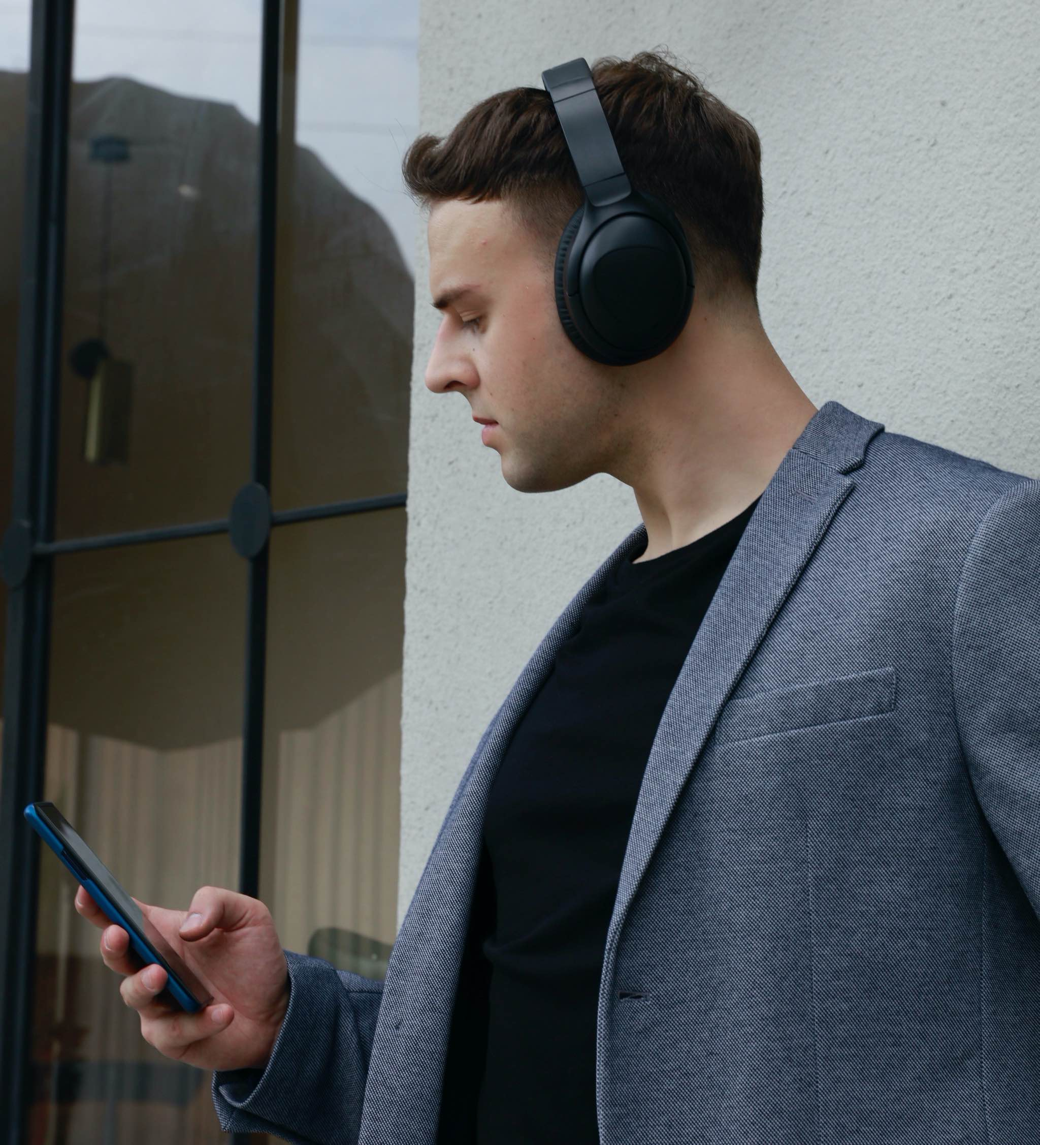 A photograph showing a young man wearing Pro Pro headphones and holding an iPhone 11 in his hand