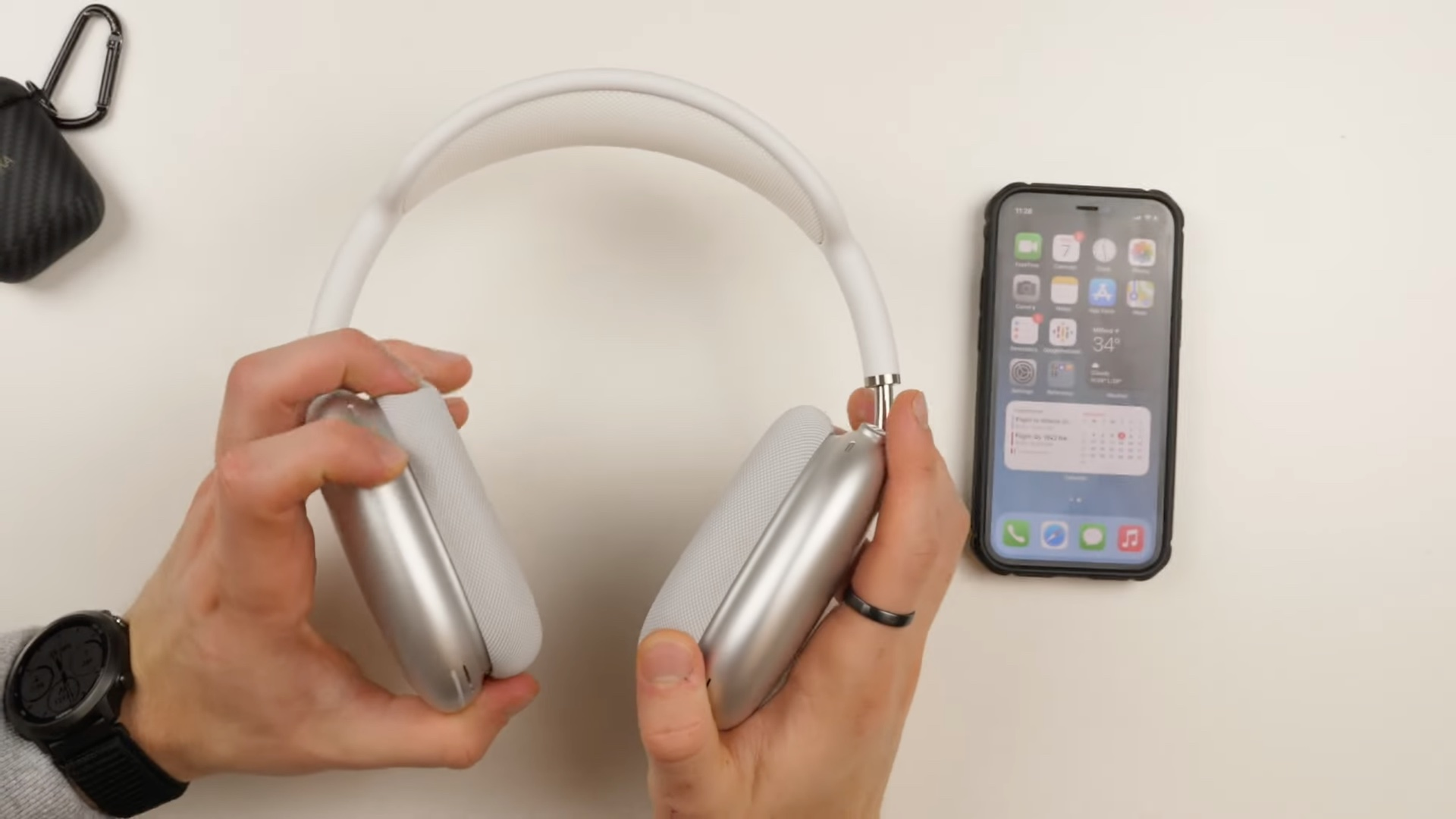 A young male's hands holding a silver pair of AirPods Max above a table