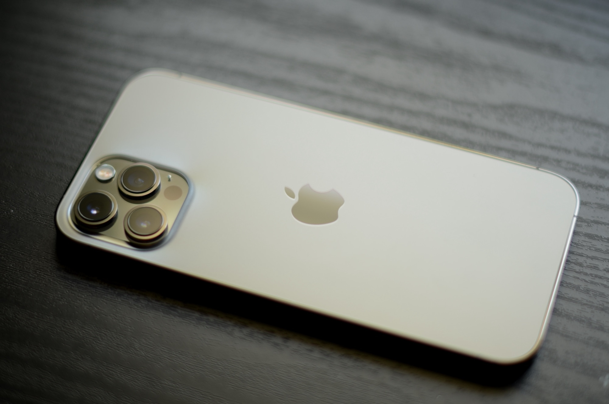 A gold iPhone 12 Pro Max laid face down on a wooden table