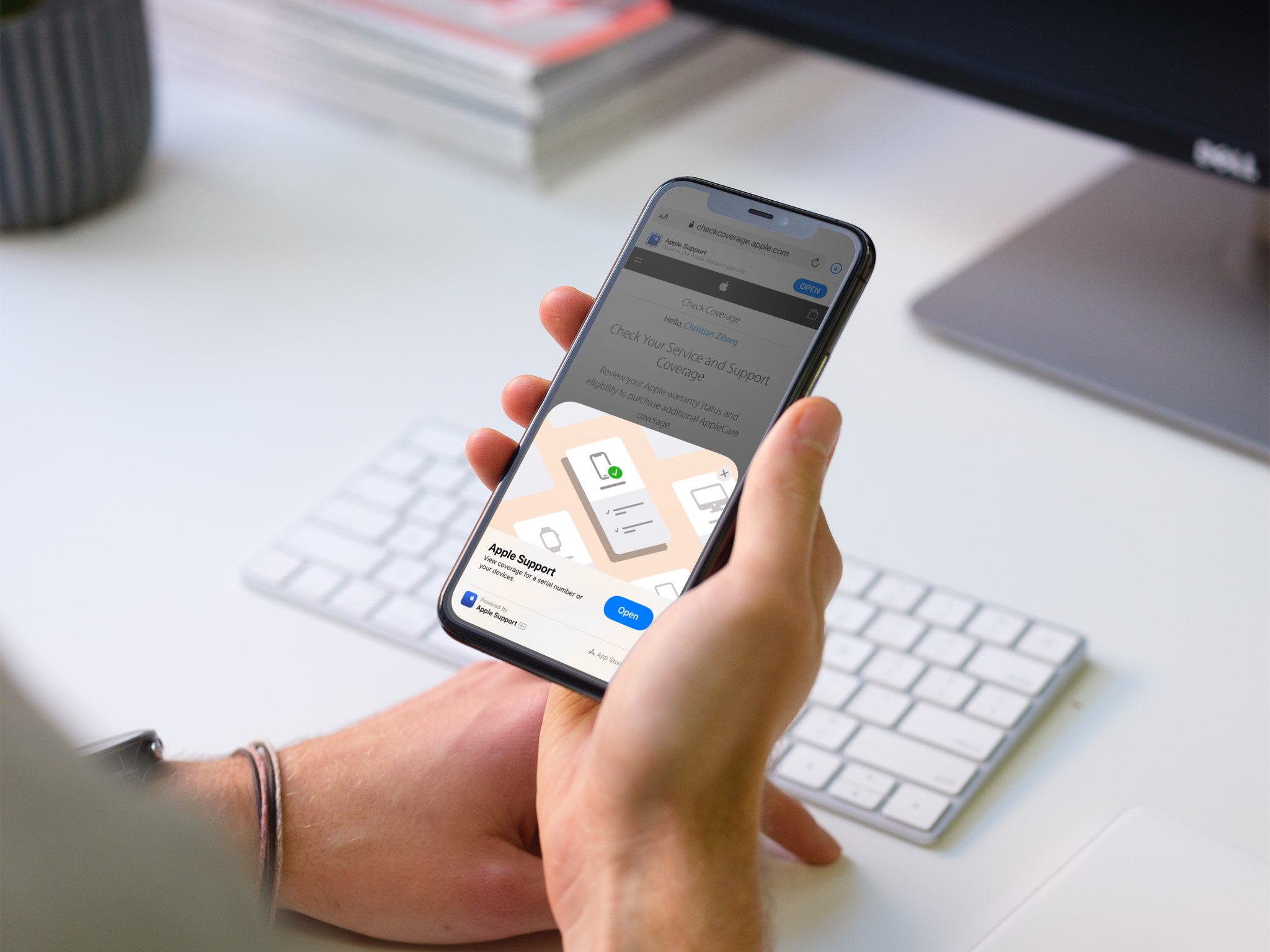 An image showing a person sitting at their desk, holding an iPhone in their hand with the Apple Support App Clip displayed on the screen