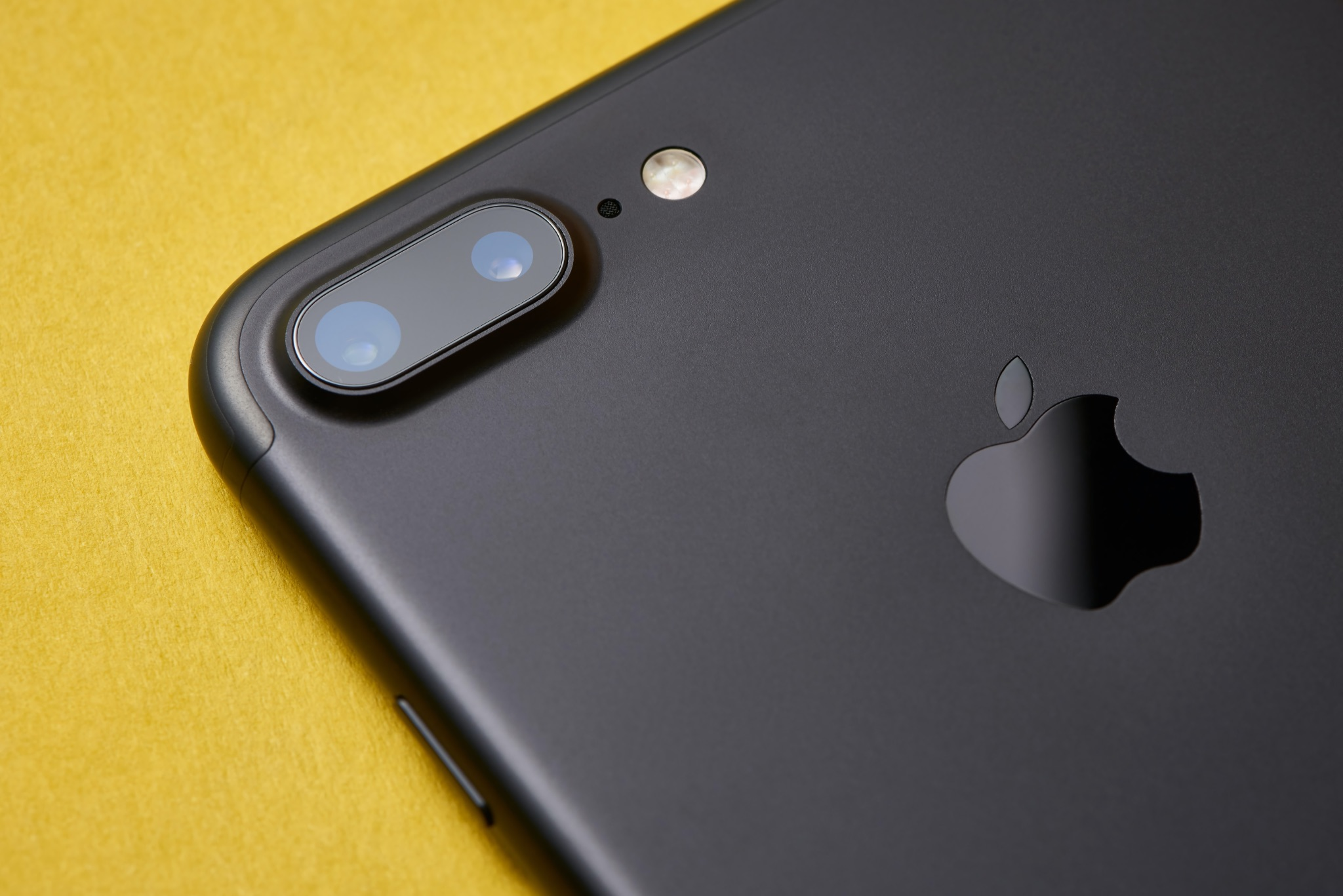 A photograph accompanying the iPhone flashlight brightness tutorial featuring a closeup of a matte black iPhone 7 Plus showing the rear dual-lens camera and LED flash detail