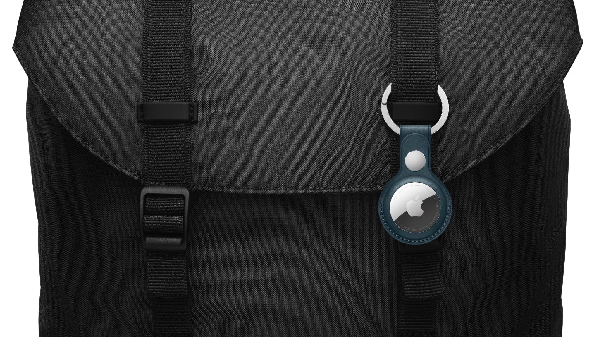 A photograph showing an Apple AirTag item tracker attached to a carrying bag