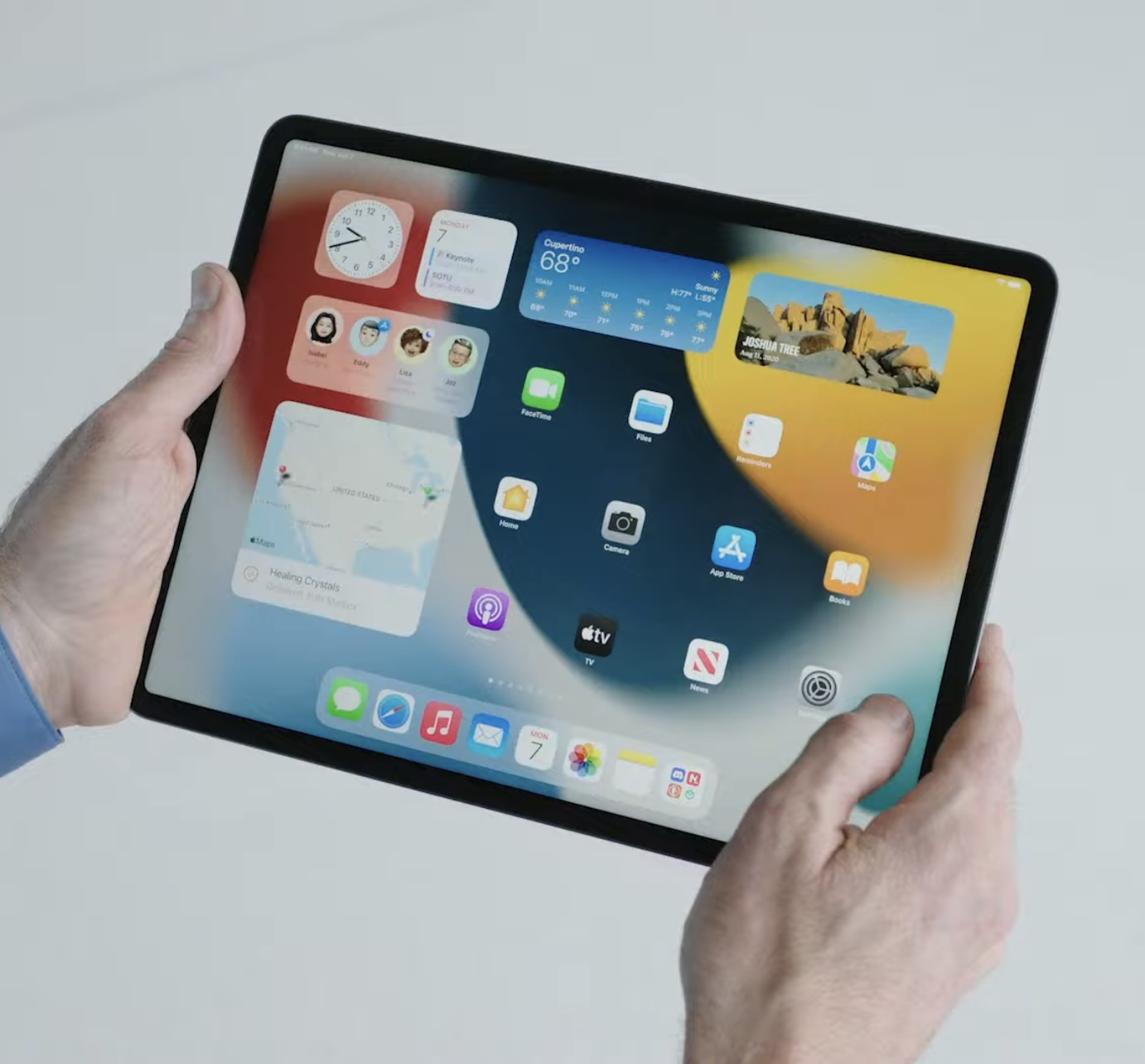 A photo showing an iPad Pro held in hands with the home screen shown with the Weather widget and other widgets and icons