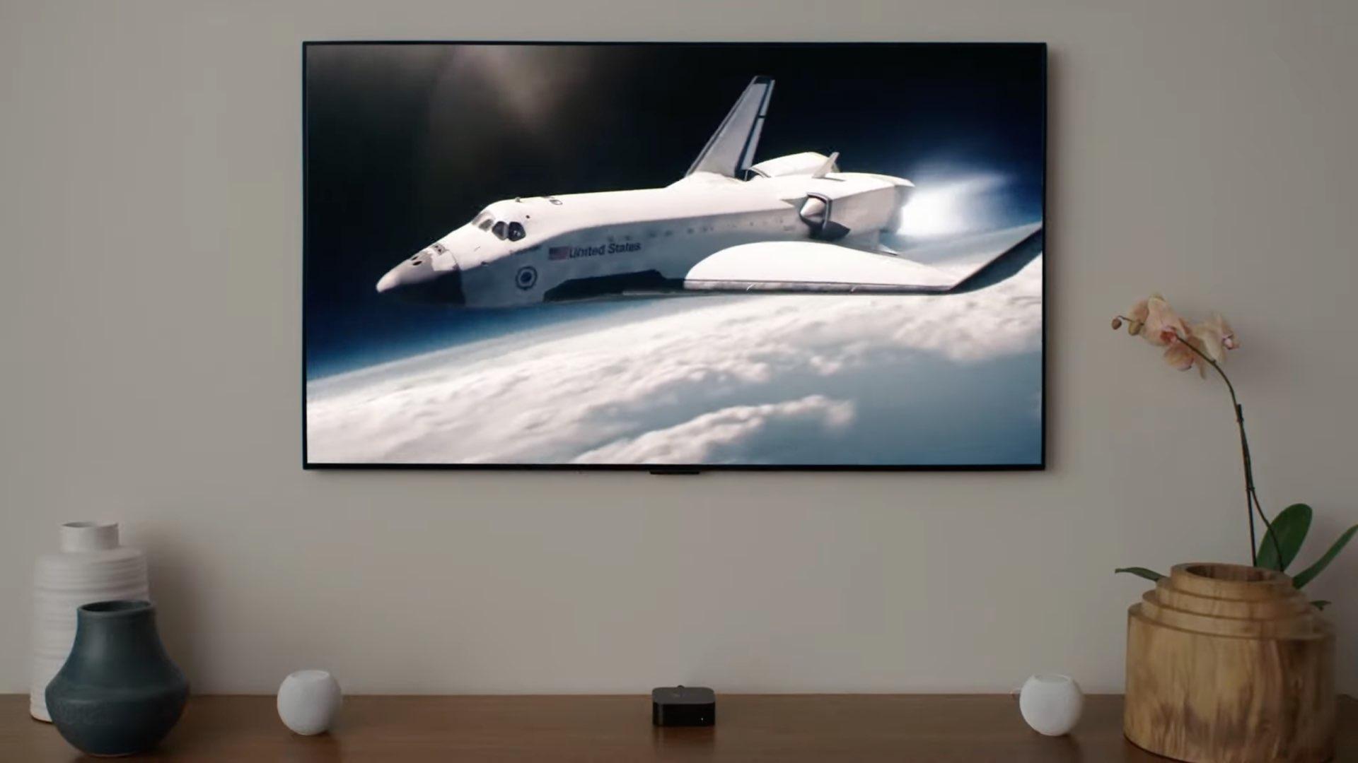 На изображении показаны Apple TV 4K и две мини-колонки HomePod в аудиосистеме домашнего кинотеатра.