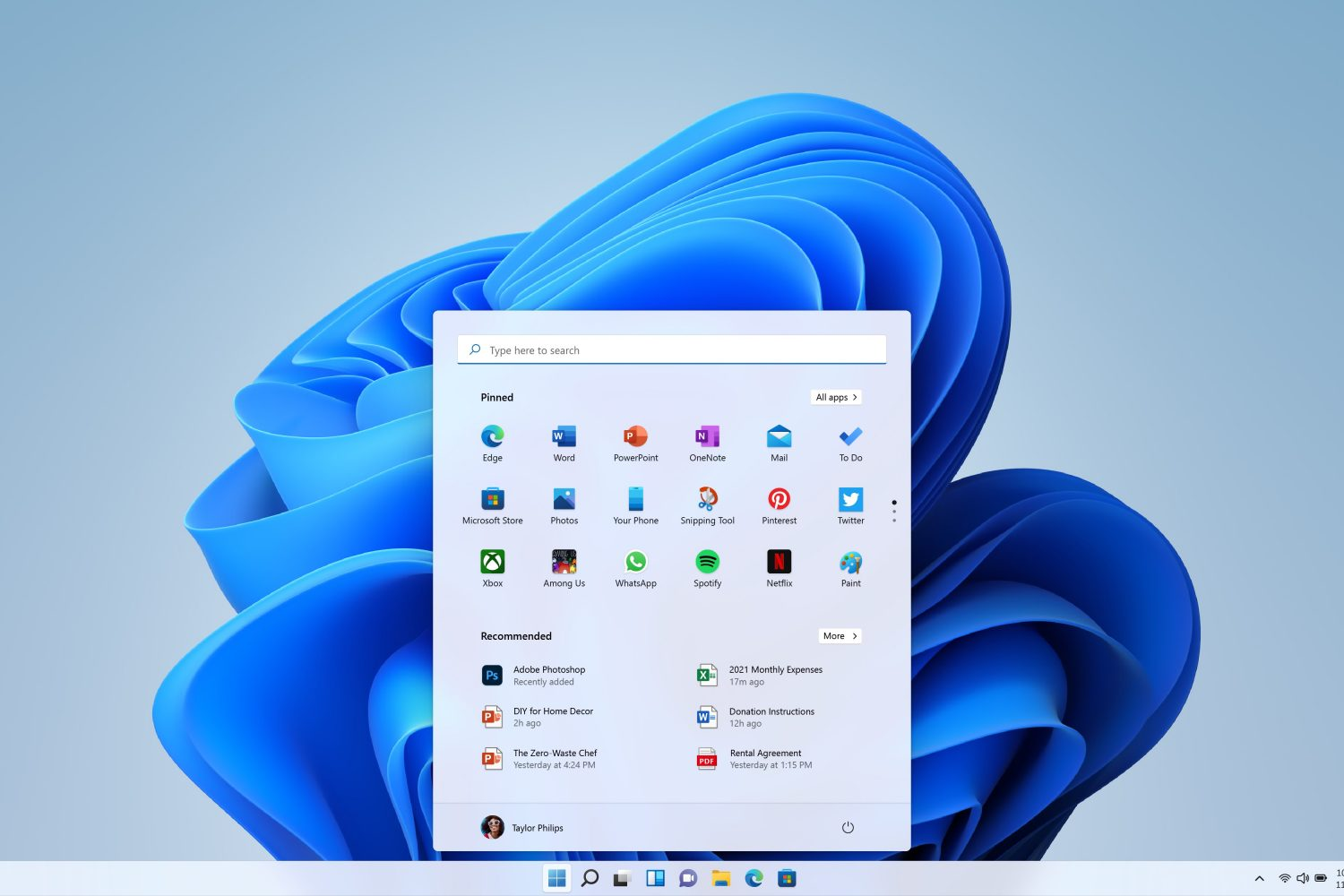 A promotional image from. Microsoft showing the Windows 11 desktop with light theme and the Start menu at the bottom center
