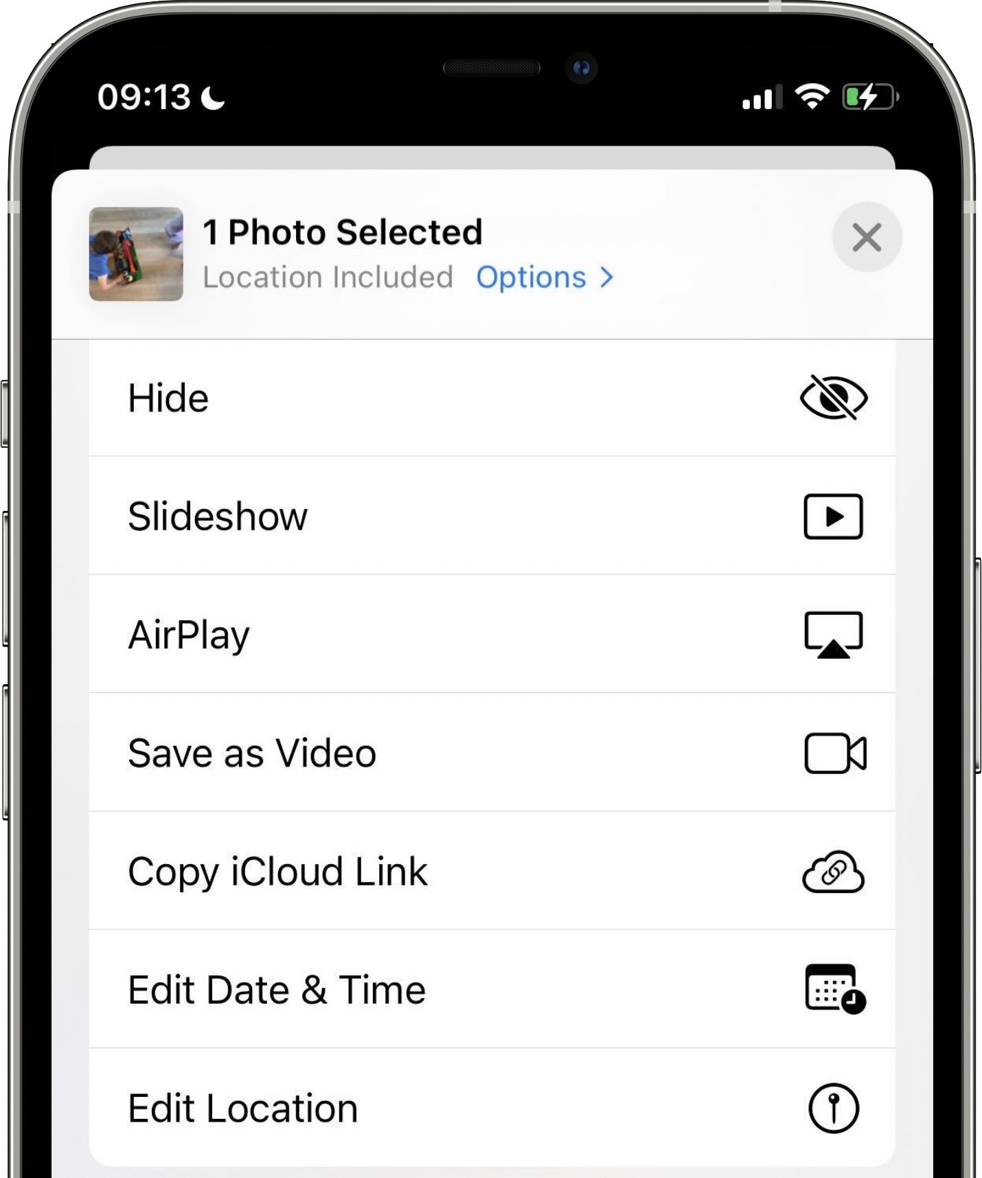 An iPhone screenshot of Apple Photos in iOS 15 with the Share menu listing options to edit EXIF metadata