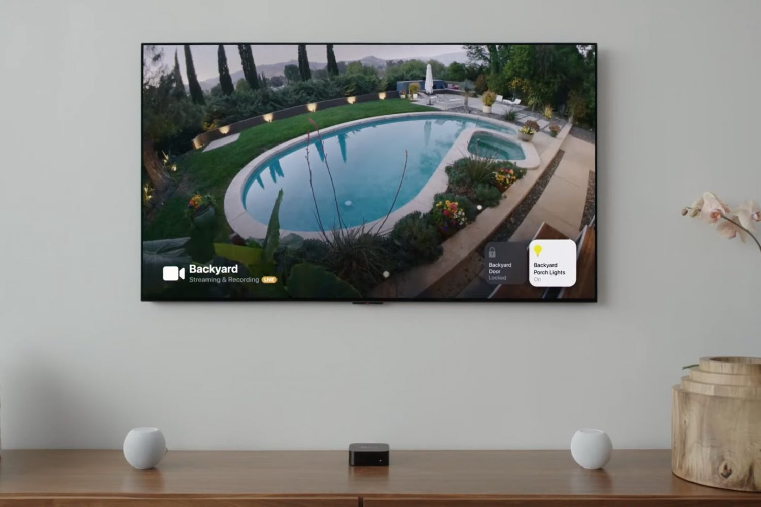 An image showing a HomeKit security camera feed displayed on Apple TV with tvOS 15, with smart lighting controls visible in screen corners