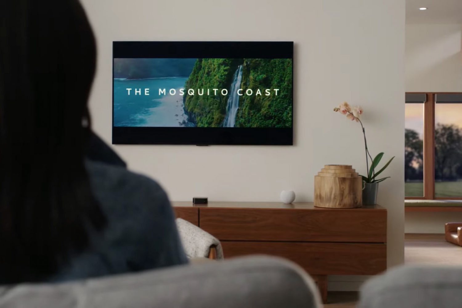 """An image showing a person sitting on a couch and watching """"Mosquito Coast"""" on their Apple TV with HomePod mini next to it"""