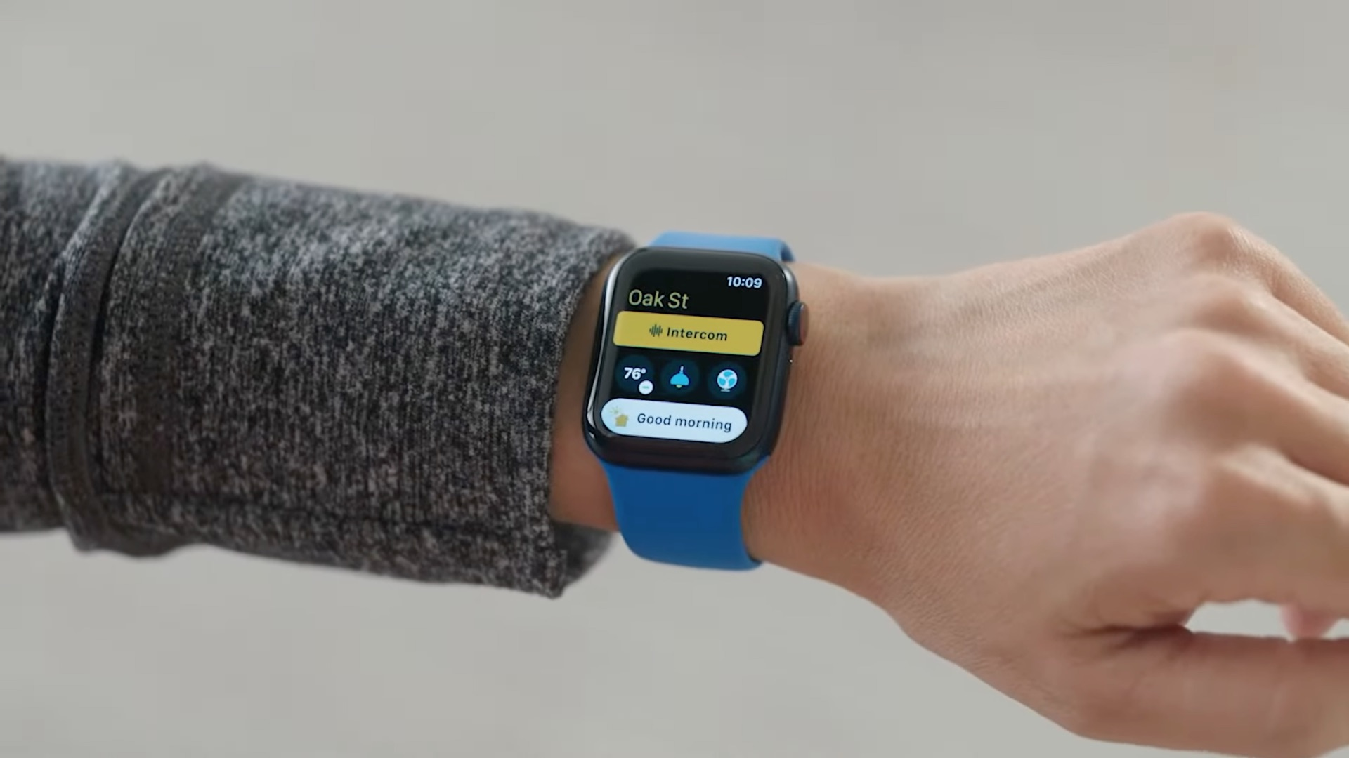 A photo showing a wrist wearing an Apple Watch running watchOS 8, with the Intercom button shown in the redesigned Home app