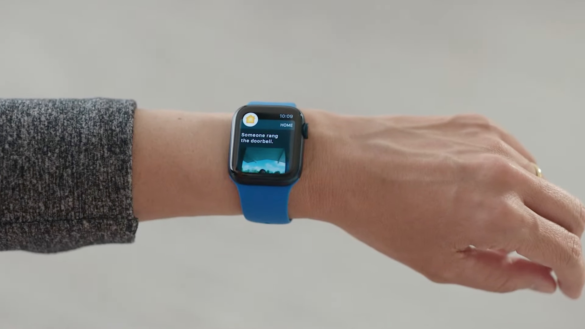 A photo showing a wrist with an Apple Watch running the Home app on watchOS 8 with the doorbell security camera video displayed on the screen