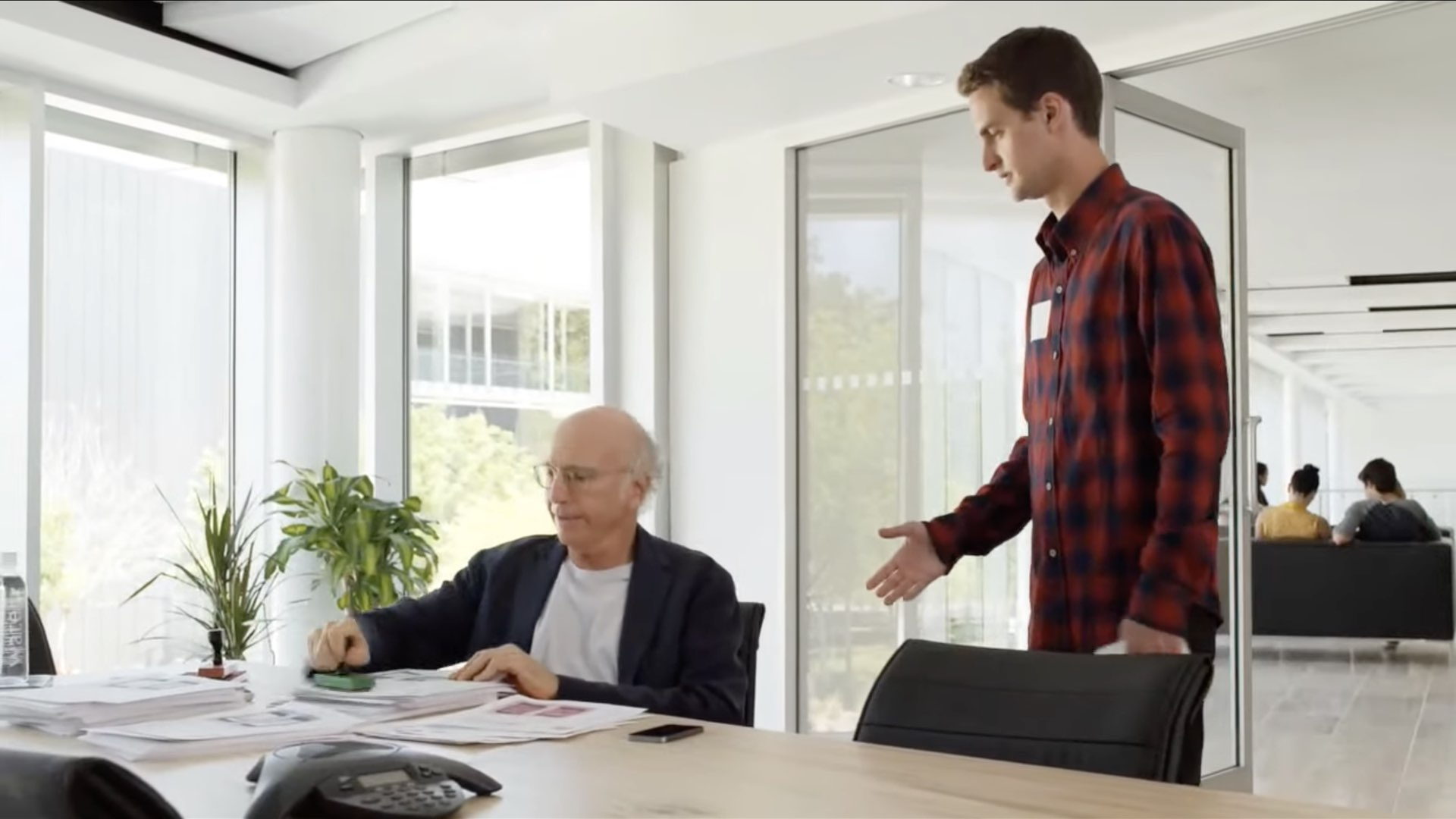 A still from Apple's unaired WWDC14 opening film showing Larry David as an app approval specialist and Snapchat founder Evan Spiegel
