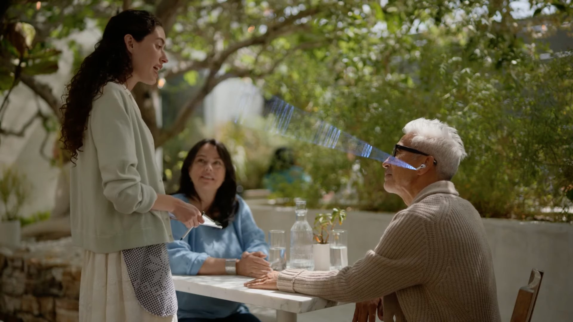 A still image from Apple's video showing an elderly person sitting at a table and talking to a waitress using her AirPods Pro with the Conversation Boost feature