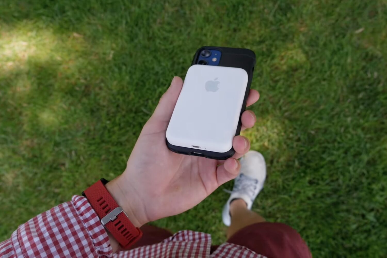 A photo showing a person walking out in the park, holding an iPhone 12 with Apple's MagSafe Battery Pack snapped onto the back