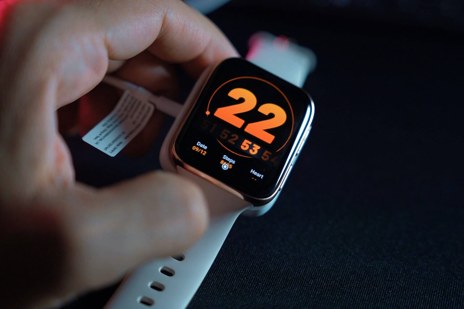 A photo of a hand holding an Apple Watch Series 6 with a white Sports band