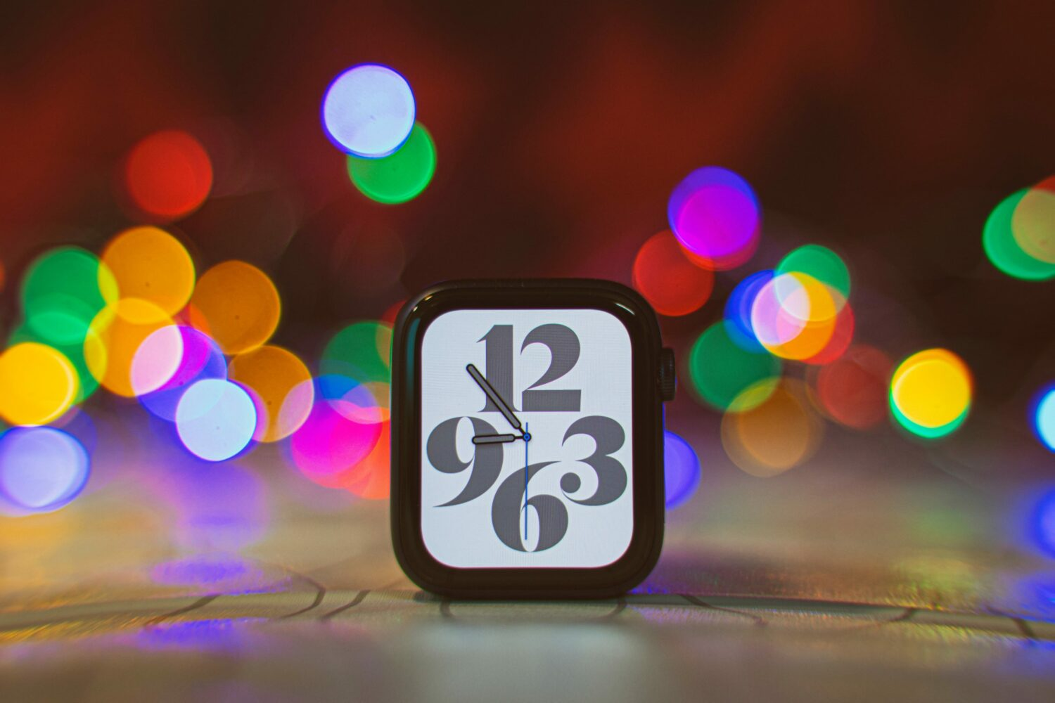 A photograph showing an Apple Watch Series 6 case sitting upright on a table, with a colorful lights in the background blurred with a depth-of-field effect
