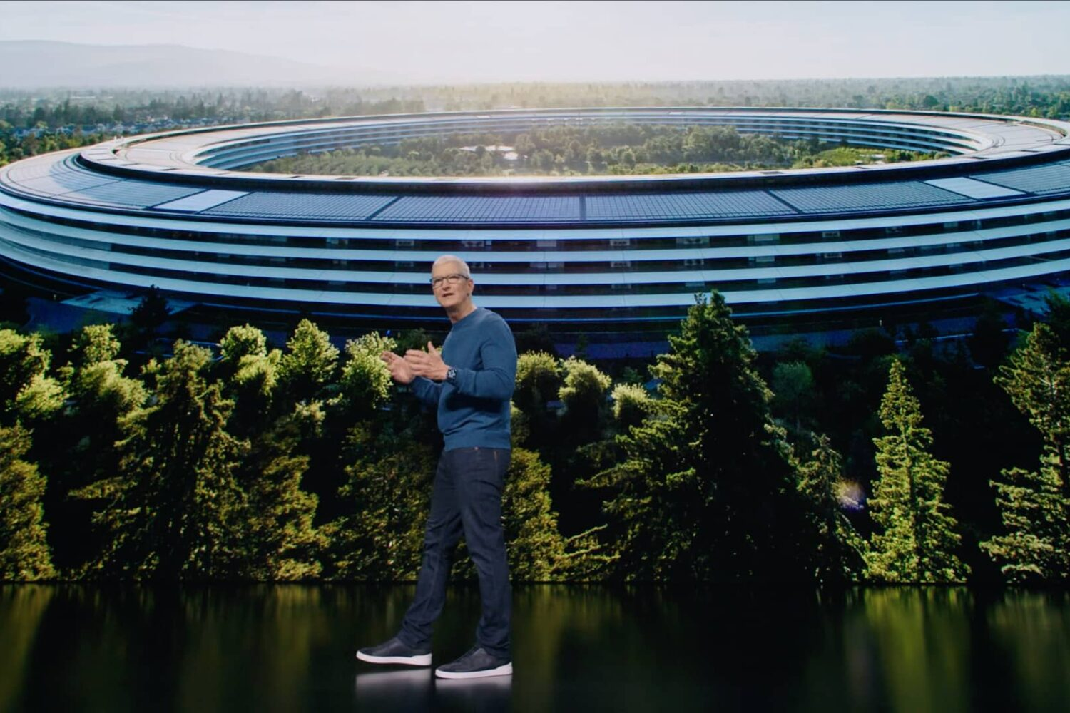 """A still image from Apple's September 2021 """"California Streaming"""" event video with CEO Tim Cook standing on stage in front of a huge keynote slide behind him that displays an aerial view of the Apple Park headquarters while Cook is talking enthusiastically and gesturing with his hands"""