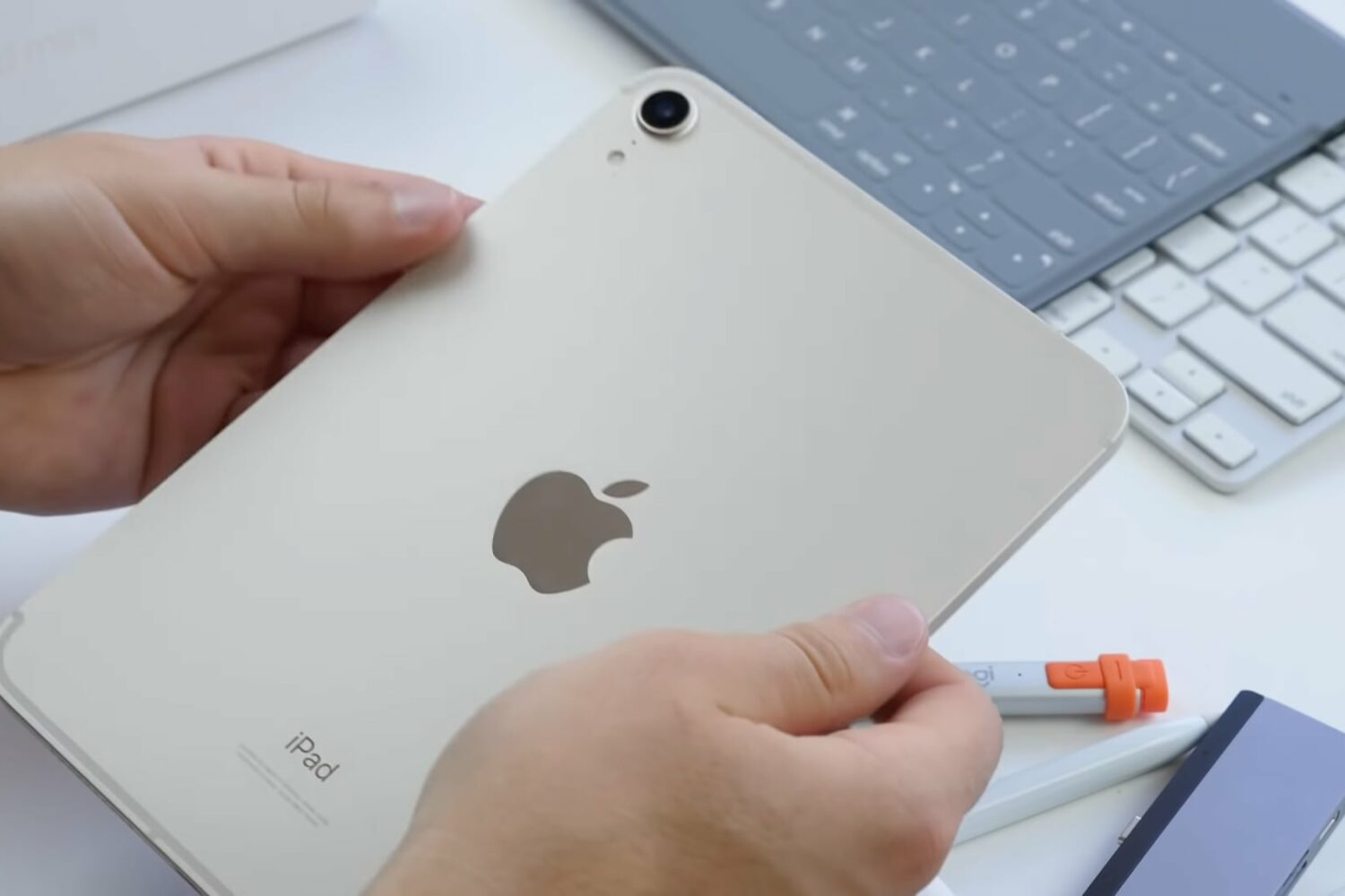 A photo showing a young male's two hands holding iPad mini 6 in Apple's Starlight color to show the tablet's back along with the Apple logo to the viewer