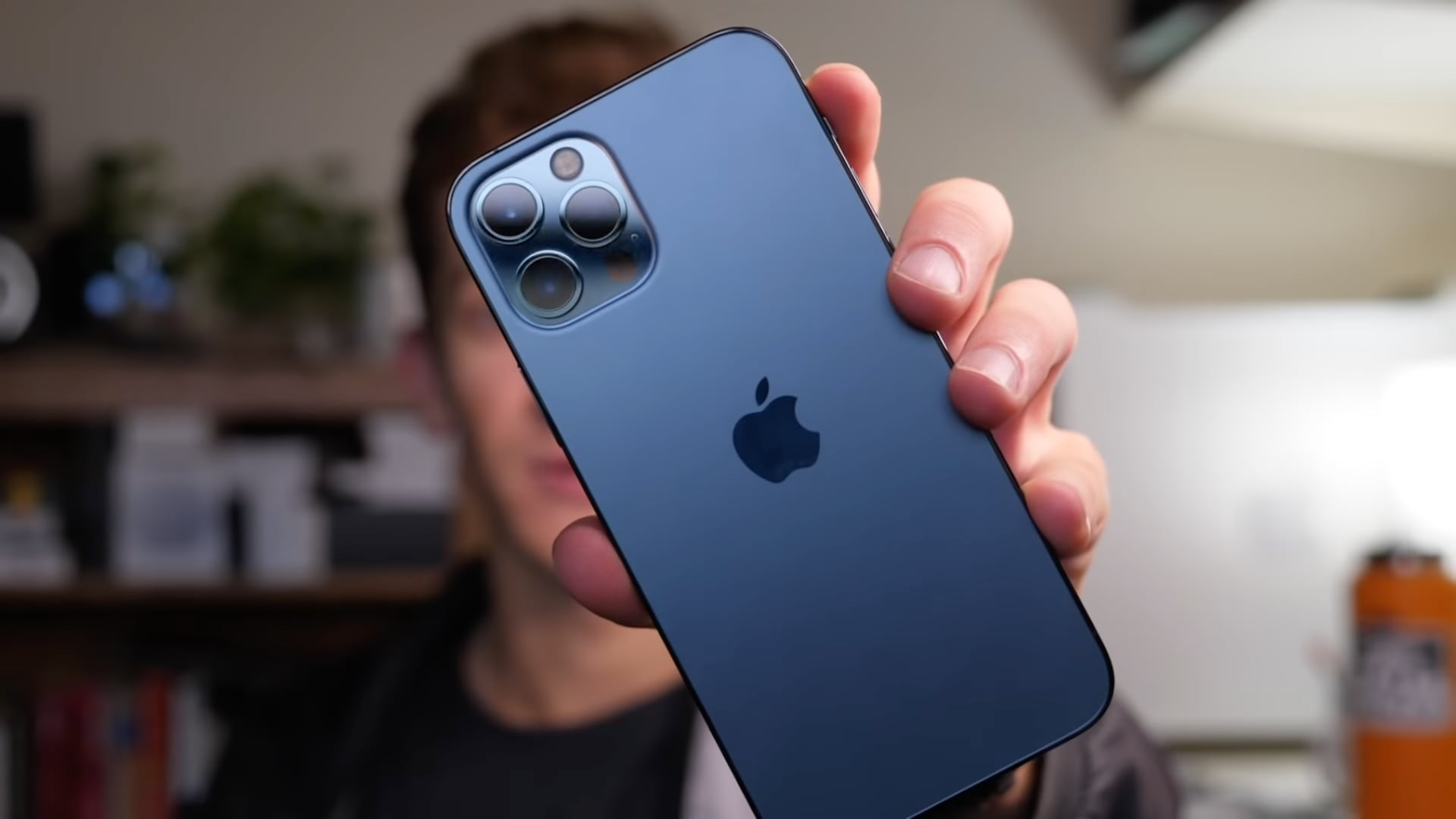 A still image taken from iDownloadBlog's video about 10 hidden iPhone 13 features, with host Harris Craycraft showing a blue iPhone 13 Pro Max in his hand to the camera