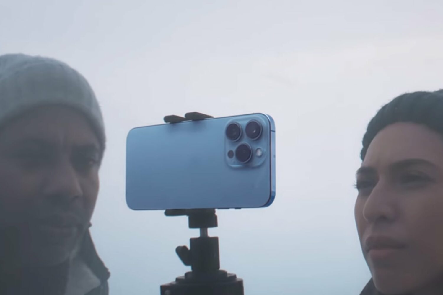 A still image taken from Apple's iPhone 13 Pro introduction video on YouTube, showing a closeup of two crew members shooting a winter scene using a tripod for the handset