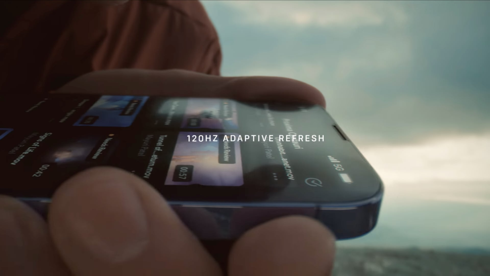 """Image from Apple's YouTube video showing ProMotion technology in action, with a hand holding an iPhone 13 Pro and scrolling through a list and the title """"120Hz adaptive refresh rate"""" overlaid on top"""
