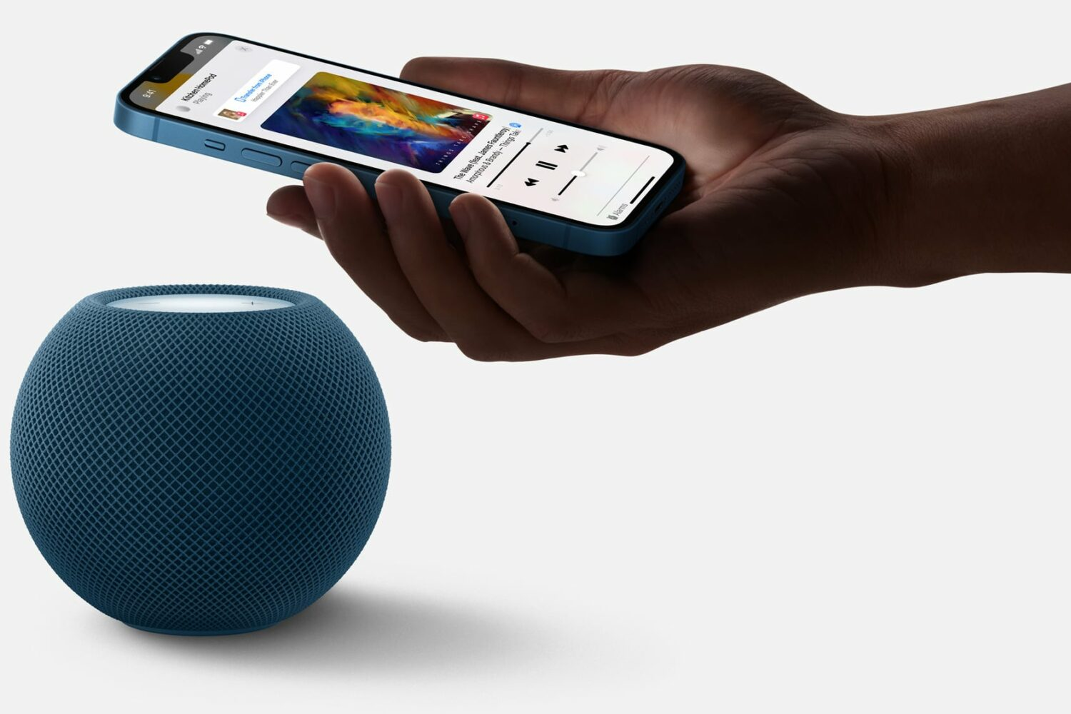 Apple's marketing image showing a male hand holding an iPhone near to a blue HomePod mini to transfer music