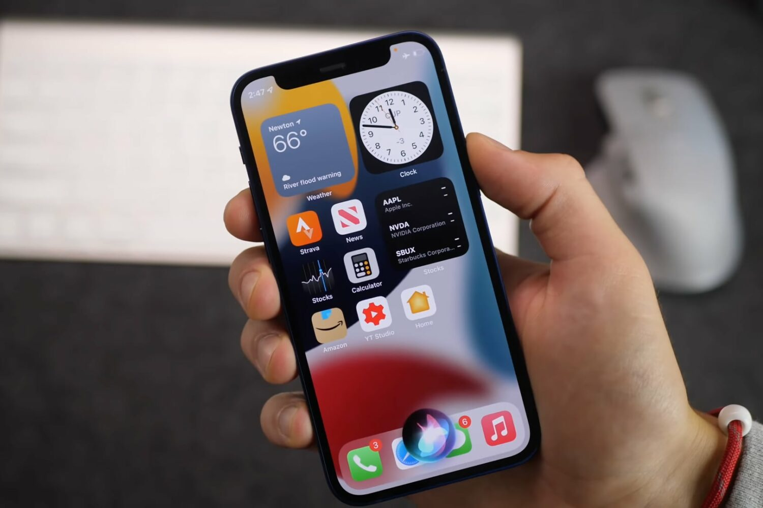 An image showing a young male's hand holding an iPhone 13 with iOS 15 home screen